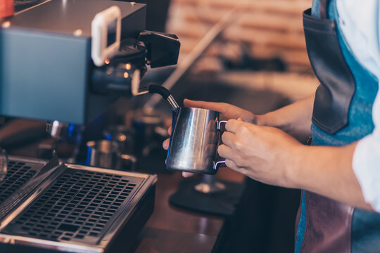 Barista heats milk steam for making lattes at coffee shop.