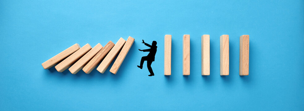 Silhouette of a man in panic against collapsing wooden dominos on blue background. Business crisis and failure concept