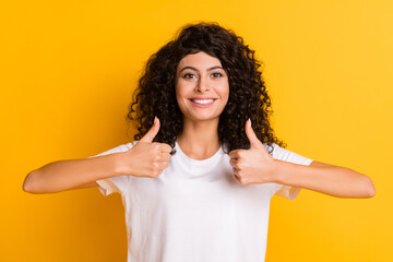 Fototapeta Photo of young beautiful smiling positive lovely pretty girl showing thumb-up isolated on yellow color background