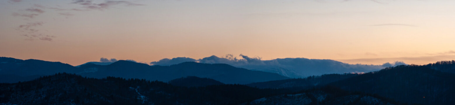 Panorama of the silhouette of mountains and forest on the background of sunset