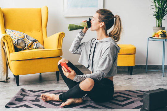 Beautiful woman drinking smoothie to refresh after workout.