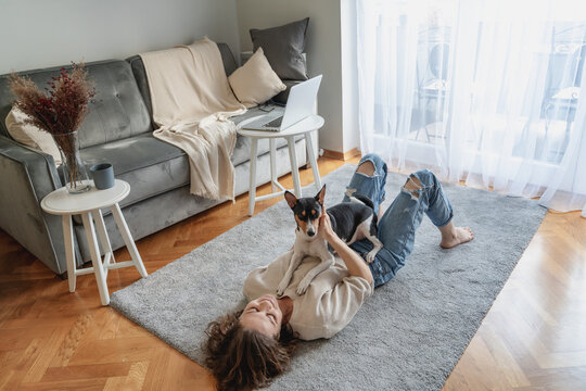 Pretty curly happy young woman smiling while lying at home on carpet with her dog