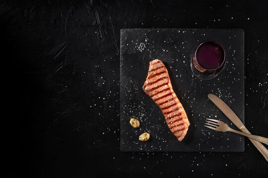 Grilled beef steak with red wine, overhead shot on a dark background with a place for text