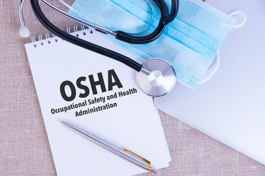 OSHA Occupational Safety and Health Administration, the text is written in a notebook, next to a pen, a disposable medical mask and a laptop on a linen background.
