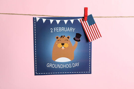 Happy Groundhog Day greeting card and American flag hanging on pink background