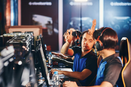 We are winning. Two happy male cyber sport gamers giving high five to each other, celebrating success while participating as one team in eSports tournament