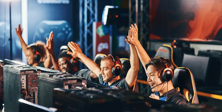 Celebrating success. Team of happy proffesional cyber sport gamers giving high five to each other while participating in eSports tournament