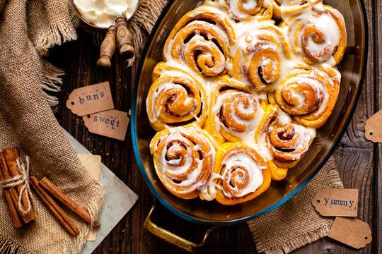 Tasty orange cinnamon swirled buns with white glaze on top