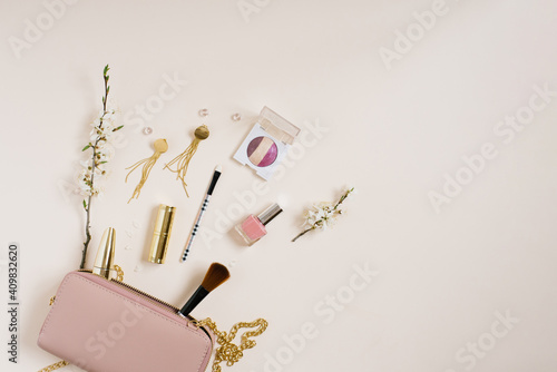 Women's desk with cosmetics, which lies next to a pink bag or cosmetic bag with copying space, apple tree flowers on a beige background. The composition of the frame for mother's day or for a blogger.