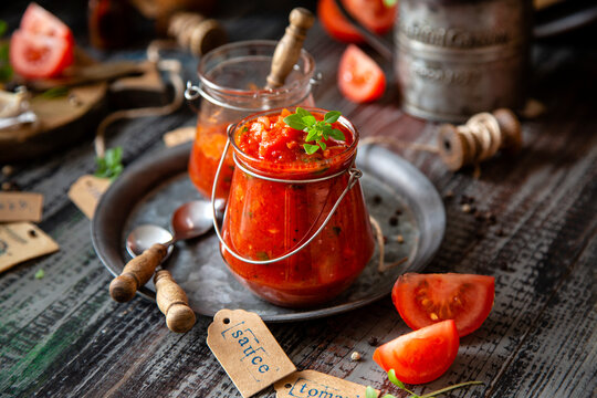 homemade red tomato sauce in glass jar on metal plate on wooden table with basil leaves