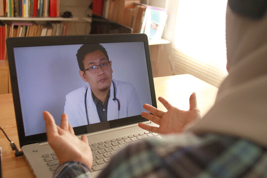 Online medical healthcare services, muslim woman doing video call with male doctor, telehealth, telemedicine consultation