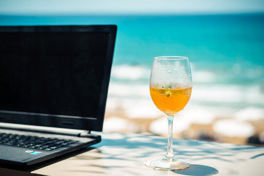 Working with laptop and drinking cocktail by the beach