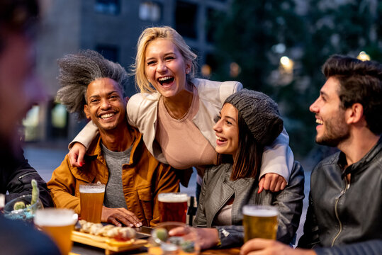 group of friends smiling and drinking at brewery, meeting of couple of millennials toasting with beers and eating fusion food, nightlife and social gathering of young people after covid19 outbreak