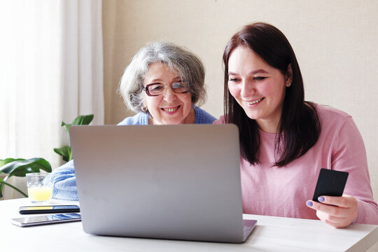 A daughter with an elderly mother makes online purchases - Helping the elderly to use a laptop computer and modern technologies - Safe shopping for self-isolation during the coronavirus epidemic