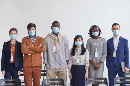 Multi-ethnic group of business people wearing masks and looking at camera while standing in row against white in conference room