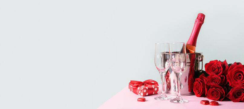 Valentine's day greeting card with gift and red sparkling wine on blue. Banner with copy space.