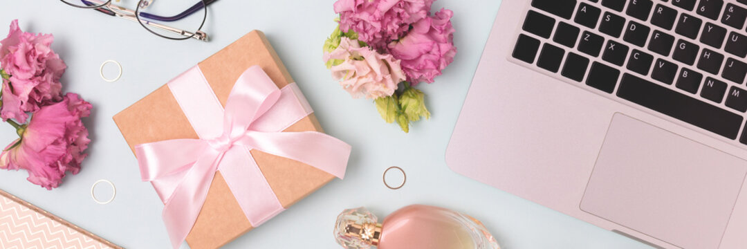 Banner with gift, laptop, flowers on a blue background. Online shopping or celebrate concept.