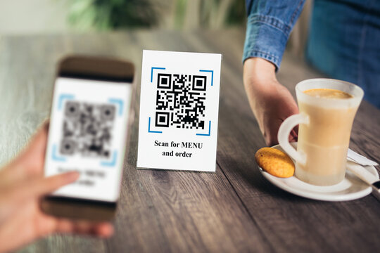 Women's hands are using the phone to scan the qr code to select menu. Scan to get discounts or pay for coffee. The concept of using a phone to transfer money or paying money online without cash.