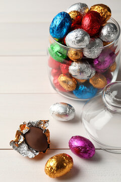 Glass jar with chocolate eggs wrapped in colorful foil on white wooden table