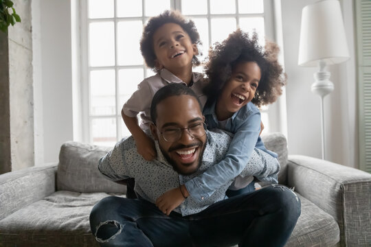 Close up overjoyed African American man wearing glasses piggy backing kids, sitting on couch at home, excited laughing dad carrying adorable little son and daughter, family having fun, funny activity