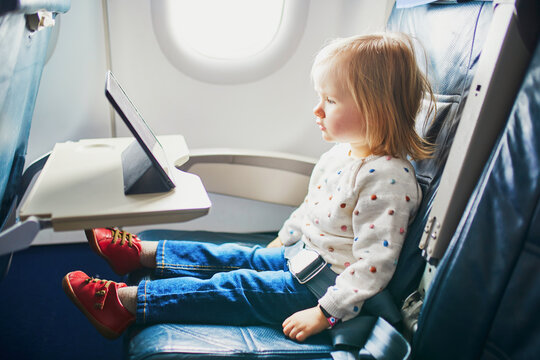 Adorable little toddler girl traveling by plane