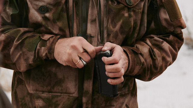 A shooter with a gold ring on his finger (married or engaged) loads 5.45x39mm rounds