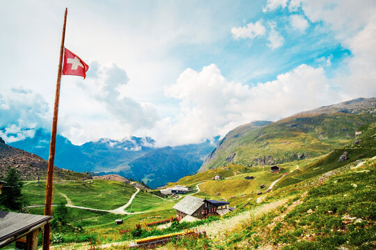 Panoramic view of alpine meadow with buildings and swiss flag
