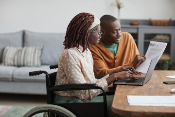 Obraz Side view portrait of young African-American woman using wheelchair working from home with husband helping her copy space - fototapety do salonu