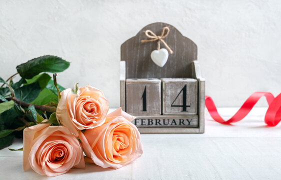 Wooden perpetual calendar on date February 14 and a bouquet of roses. Symbols Valentine's Day. Postcard.