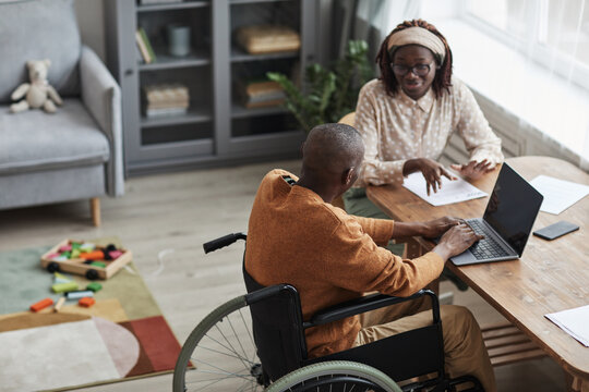 High angle portrait of African-American man using wheelchair working from home with wife, copy space