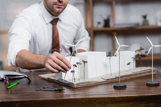 cropped view of architect holding model of wind turbine near architectural maquette, blurred background