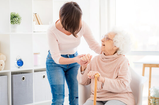 Kind woman helping lovely old lady to stand from chair