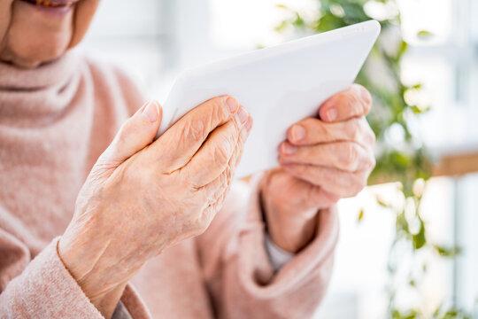 elderly woman holding white tablet