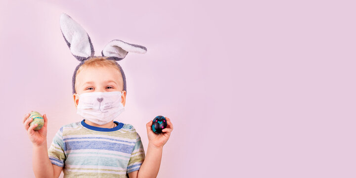Cute baby boy in rabbit bunny ears on head and protective mask with colored eggs on pink background. Covid Easter holiday banner