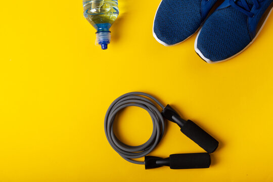 Blue sneakers, skipping rope and bottle of water on yellow background. Concept of healthy lifestile, everyday training and force of will