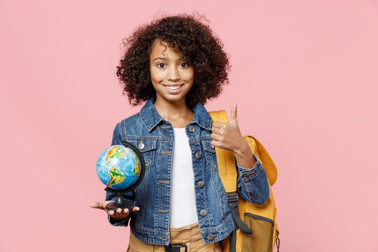 Smiling little african american kid school girl 12-13 years old in casual clothes backpack hold in palm Earth world globe show thumb up gesture isolated on pink background Childhood education concept