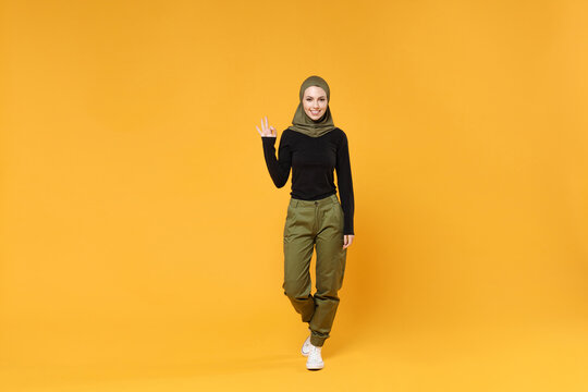Full length of cheerful young arabian muslim woman wearing hijab black green clothes showing OK gesture isolated on bright yellow color background studio portrait. People religious lifestyle concept.