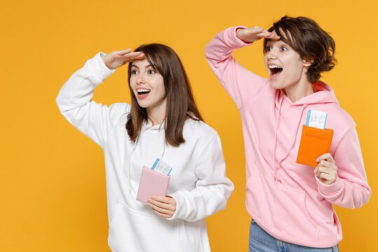 Excited two young traveler tourist women friends in casual white pink hoodies hold passport tickets holding hand at forehead looking far away distance isolated on yellow background studio portrait.