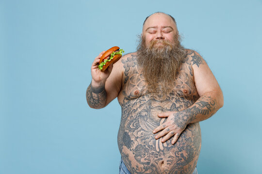 Joyful fat pudge obese chubby overweight man has tattooed naked big belly hold fast food burger put hand on stomach enjoying isolated on blue background. Weight loss obesity unhealthy diet concept.