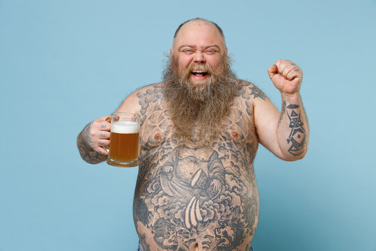 Joyful fat pudge obese chubby overweight man has tattooed naked bare big belly hold glass of beer doing winner gesture isolated on blue background studio. Weight loss obesity unhealthy diet concept.