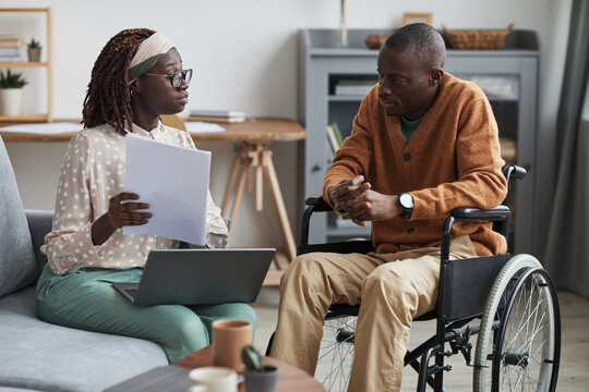 Portrait of African-American couple with handicapped man using wheelchair working from home together in modern interior
