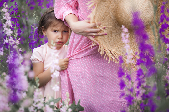 Cute little funny girl holding her mom by the dress. Shy baby