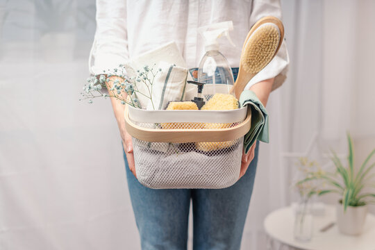 Woman holding basket with cleaning equipment. A woman is doing spring cleaning. The concept of housework and storage.
