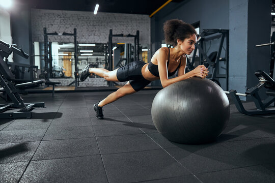 Active brunette woman leaning on fitness ball