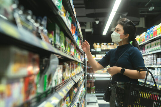 new normal after covid epidemic young smart asian female shopping new lifestyle in supermarket with face shild or mask protection hand choose consumer products new normal lifestyle