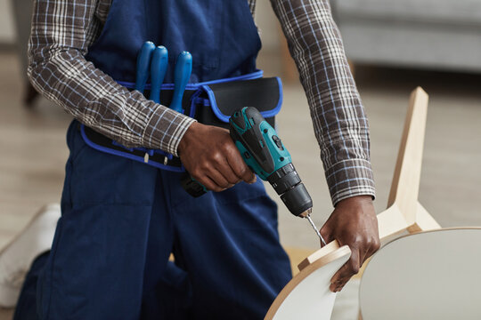 Cropped portrait of unrecognizable African-American handyman holding electric screwdriver while assembling furniture in home interior, copy space