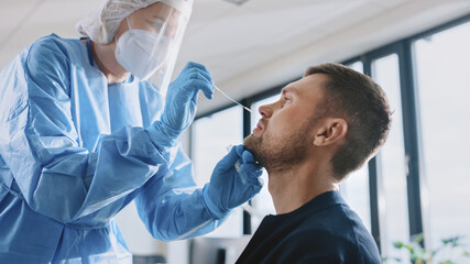 Medical Nurse in Safety Gloves and Mask, Protective Face Shield and Overalls is Taking a PCR Corona Virus Sample in a Health Clinic. Doctor Uses Respiratory Swab Test. Covid-19 Pandemic Concept.