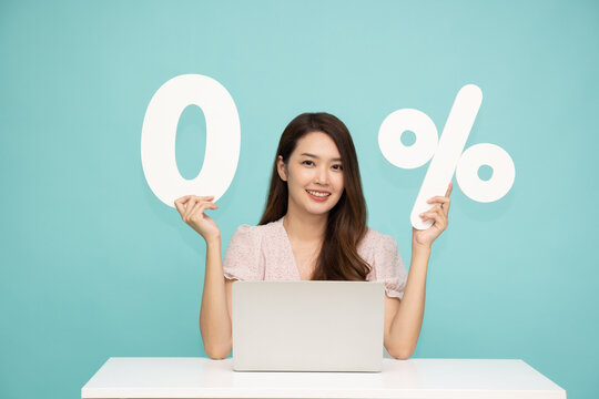 Portrait of Asian business woman showing and holding 0% number or zero percent isolated over light green background
