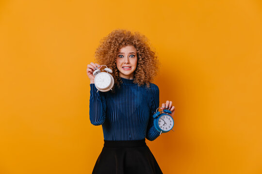 Girl with curls dressed in blue sweater feels awkward, holding two alarm clocks on yellow background
