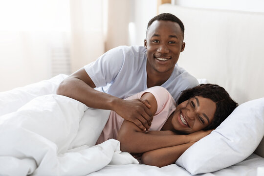 Happy black couple cuddling in bed at home